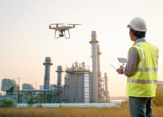 A drone hovers in front of a refinery